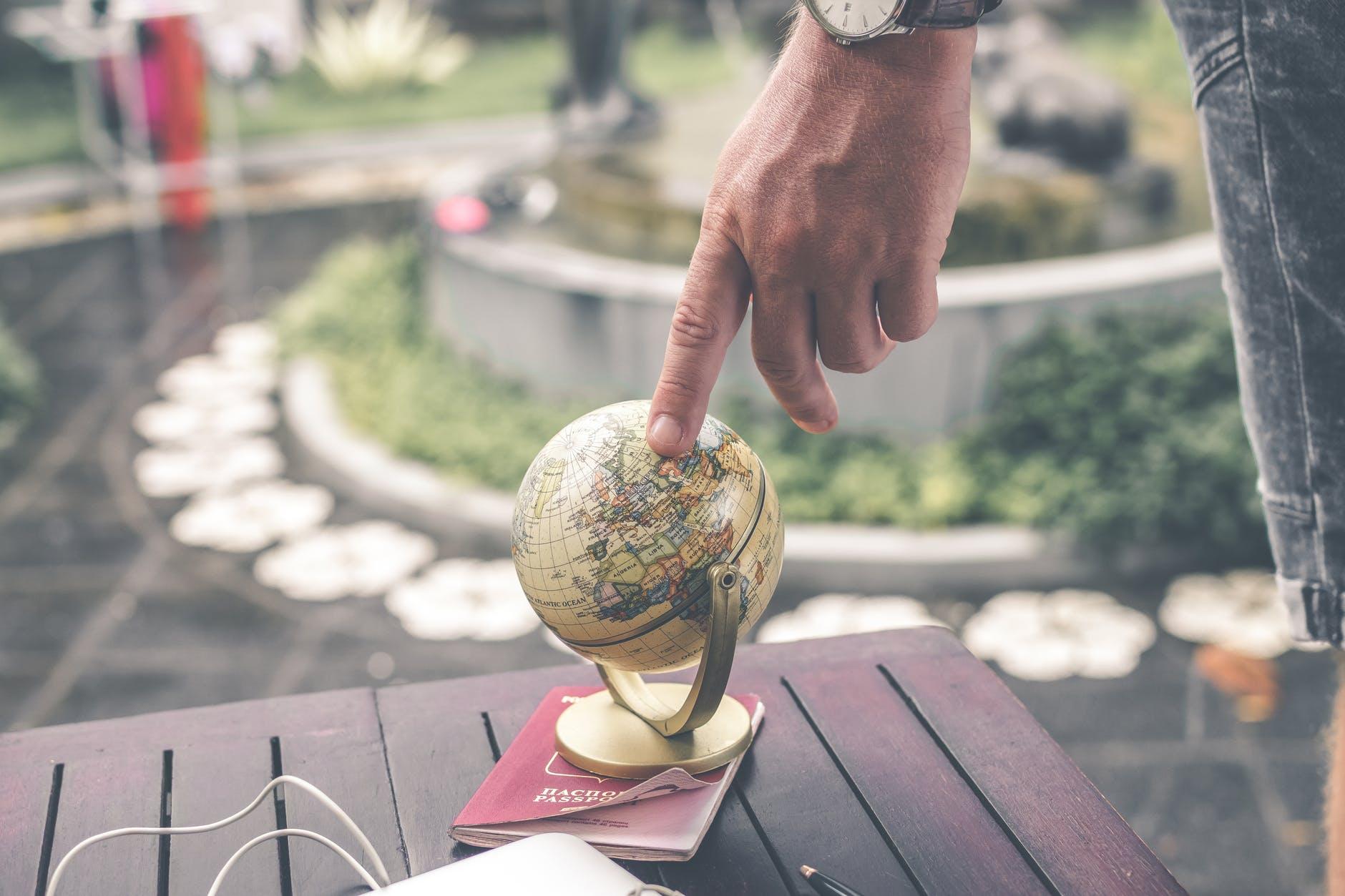 person holding terrestrial globe scale model taken