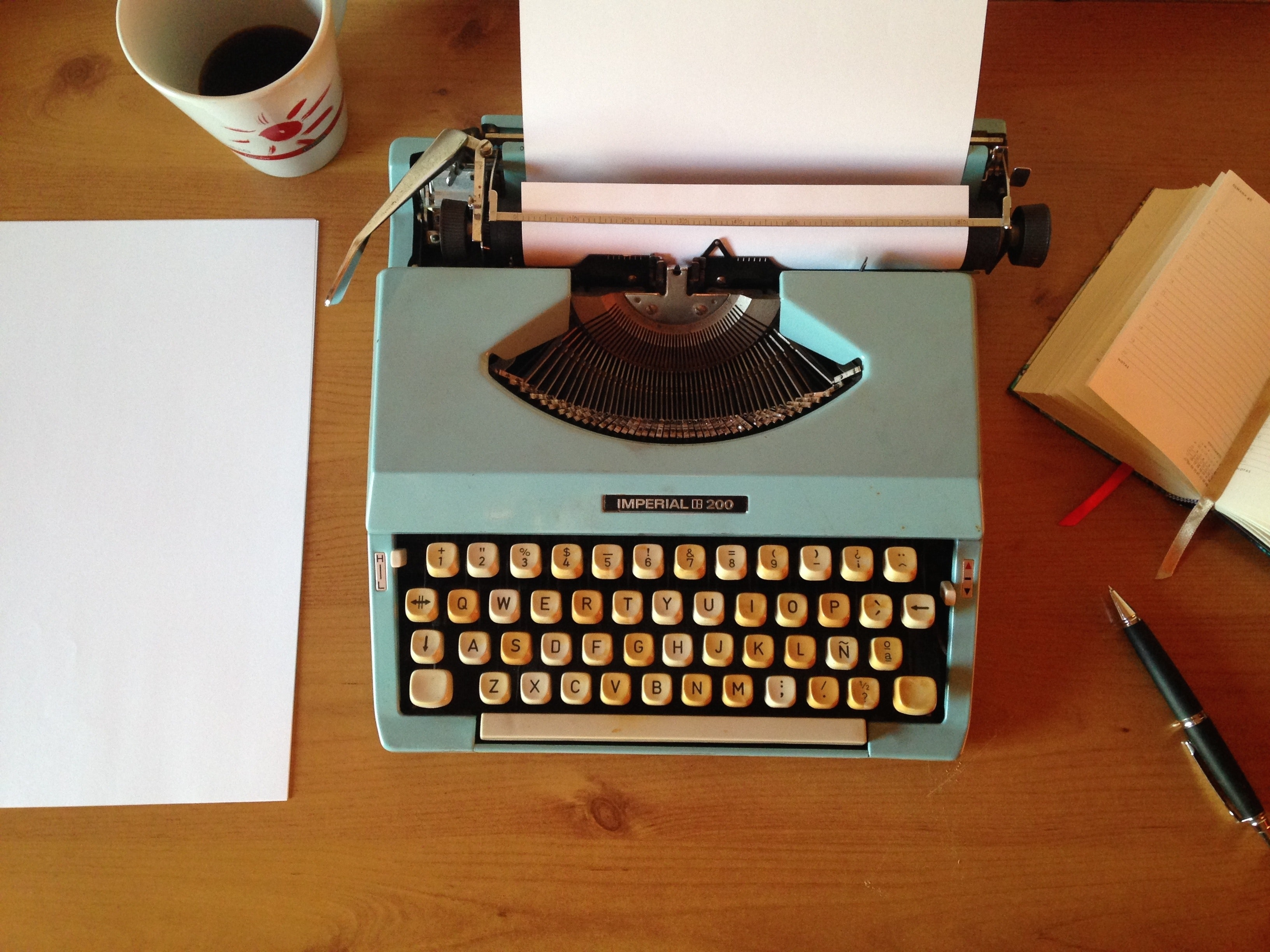 A picture of a neat desk with a typewriter.